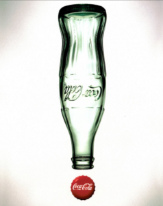 The Chesterman Company. An upside down glass Coca Cola bottle, empty with a metal Coca Cola cap below, making it look like an exclamation.
