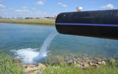 Wichita Falls Texas. A large pipe on the right with water running out of it into a pond or lake.