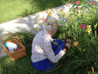 Bishop's Glen, a woman kneels in the grass along a sidewalk to do some gardening.