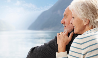 Florida Assisted Living Association. A man and woman embracing each other on the right with a mountain and water in the background and to the left.