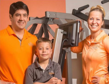 Franchise Business Review. A family poses for a photo in front of exercise equipment.