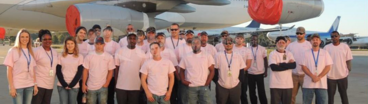 Universal Asset Management group of employees posing in front of a jet.