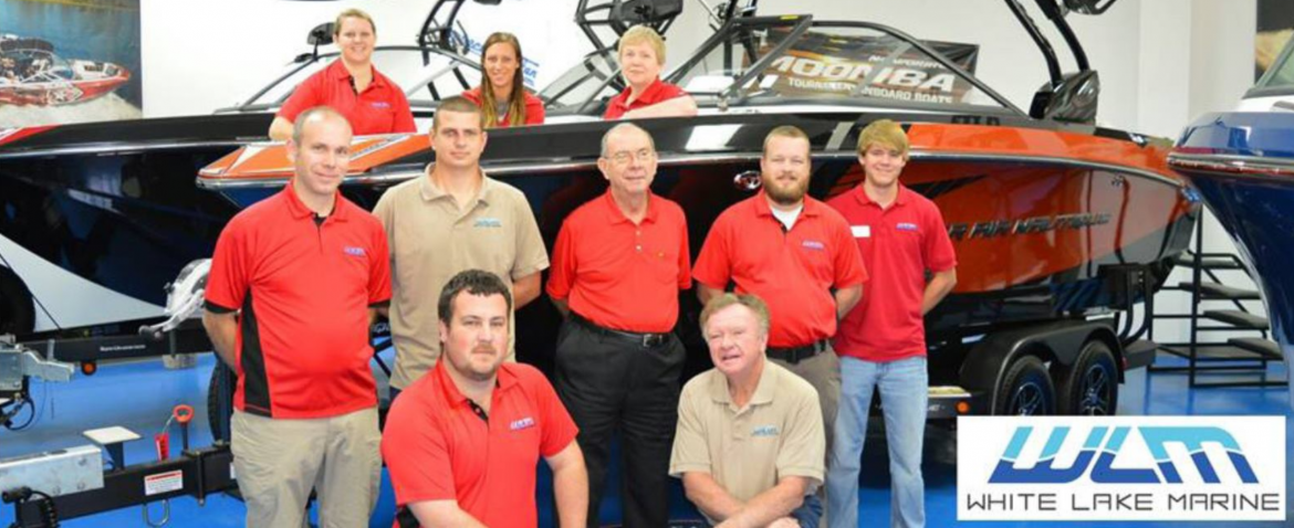 White Lake Marine employees posing for a photo in their show room in front of a boat.