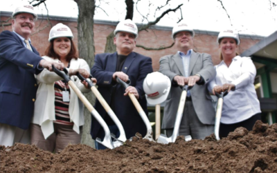 Enfield Connecticut, 5 people stand with hard hats on and holding shovels in a pile of dirt.