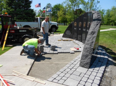 Enfield Connecticut, employees work on repaving the area around multiple plaques in granite.