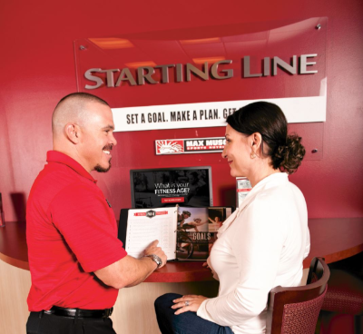A Max Muscle employee stands next to a woman sitting at a station they have set up to get started with Max Muscle.