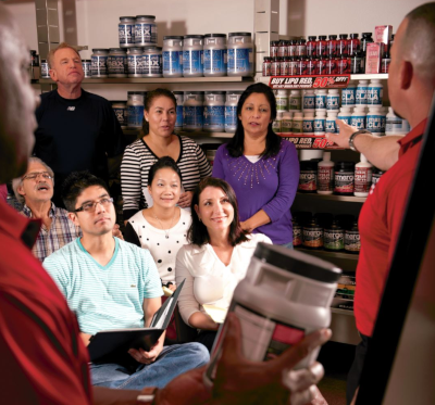 Two Max Muscle employees talk to a group of people with a board behind them and product in hand.