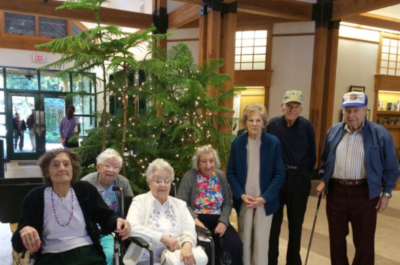 Mission Oaks residents post for a photo in the front lobby with a tree behind them.