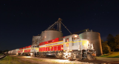An Iowa Northern Railway Company train traveling at night with lights on and metal cylinder building behind it.