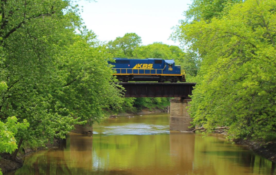 A Kankakee, Beaverville & Southern Railroad train going over a river on a small bridge with trees lining both sides of the river.