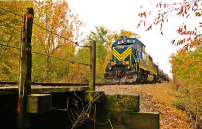 A Kankakee, Beaverville & Southern Railroad train about to pass over a small bridge with wood posts and wire along the sides.