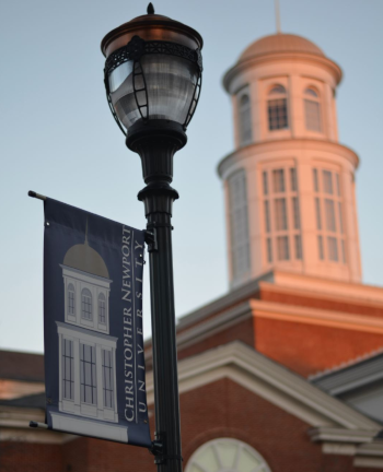 A close up on a light pole with the top of the Christopher Newport University building in the background from Newport News, Virginia.