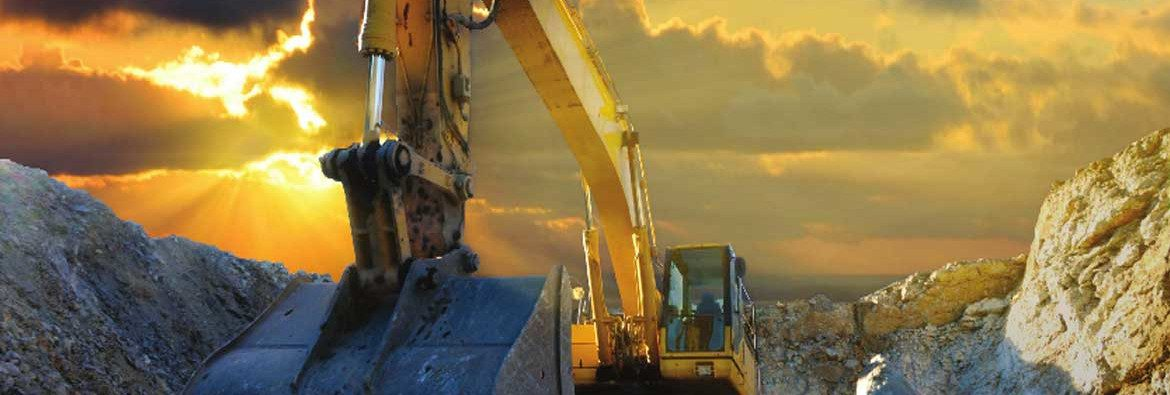 Lydford Mining Company. An excavator working with the sun behind clouds creating an orange sky.