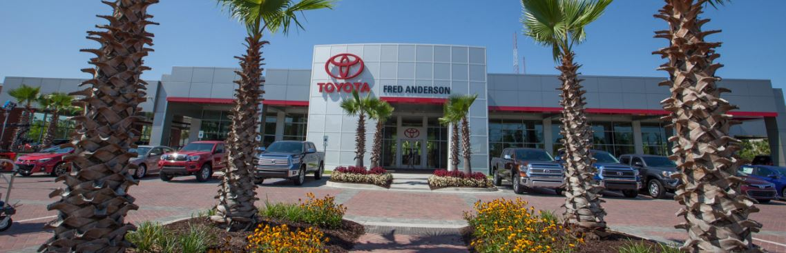 Anderson Automotive Group, front of their Fred Anderson Toyota dealership with cars lined up out front and palm trees on the sides of a walkway in the foreground.