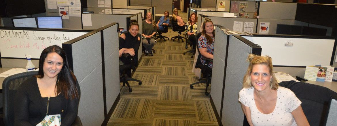 The Remi Group office photo of employees sitting and leaning outside of their cubicles for a photo.