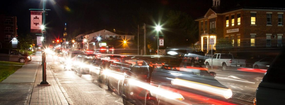 Clarence-Rockland, Ontario. A view of a city street at night with cars blurred in motion.