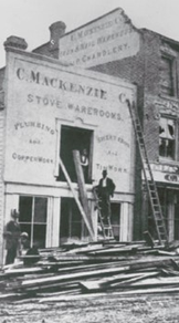 Mackenzie Milne. Old black and white photo showing people working at a Mackenzie building with piles of wood and ladders up.