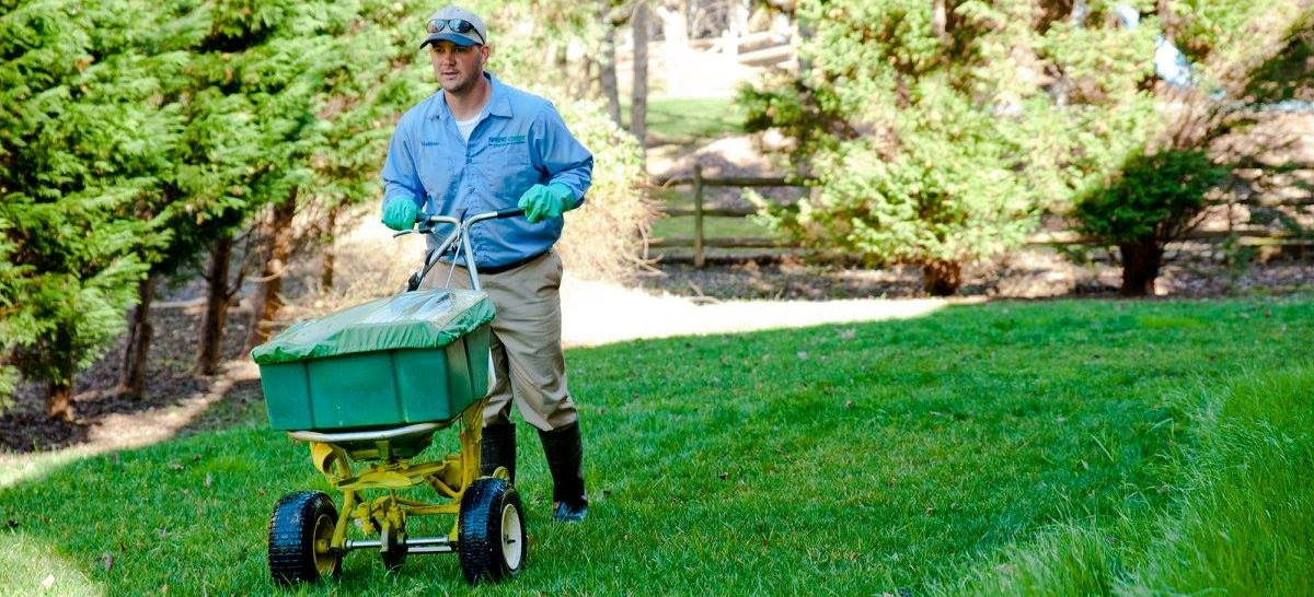 Spring Green Lawn Care A Man Using Spreader On