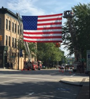 Cleveland, Tennessee. Two firetrucks lifting an american flag hanging across the city street.