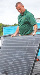 Werner Electric Ventures. A man holds a solar panel while on a rooftop.