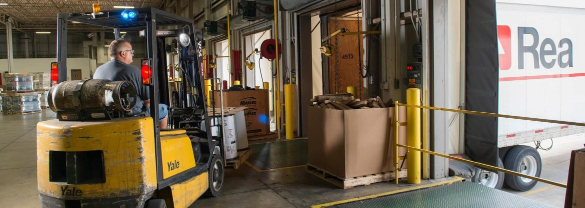 A forklift loading materials onto an Rea Magnet Wire truck.