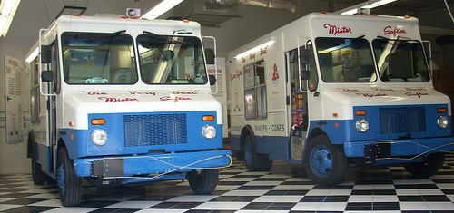 Mister Softee ice cream trucks parked on a checkered floor.