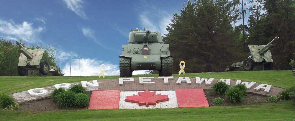Petawawa Garrison. A tank and two artillery pieces in a green field with landscaping and stones in front that says GRN PETAWAWA with a Canadian flag in front.