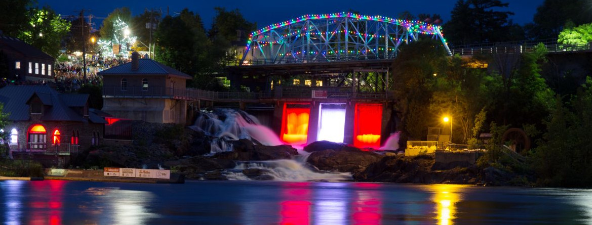 A nighttime view of water falls in Bracebridge Ontario, with a lit up bridge.