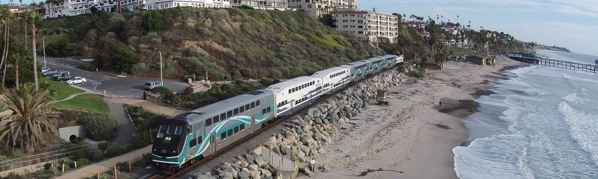 Metrolink, a train travelling on tracks along a beach with a hill and multi story buildings behind.