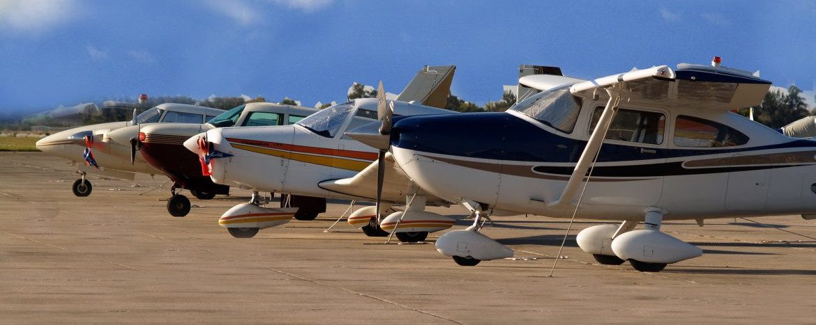 Sebring Regional Airport & Commerce Park with a row of single prop planes in a row on the tarmac.
