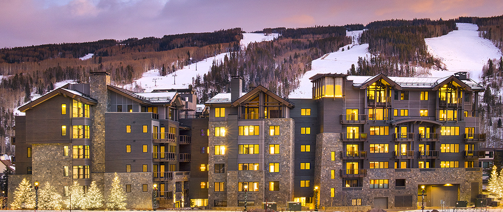 Slifer Smith Frampton Real Estate photo of a large multi story residential building with interior lights on in each unit glowing, and a hill with snow behind it.