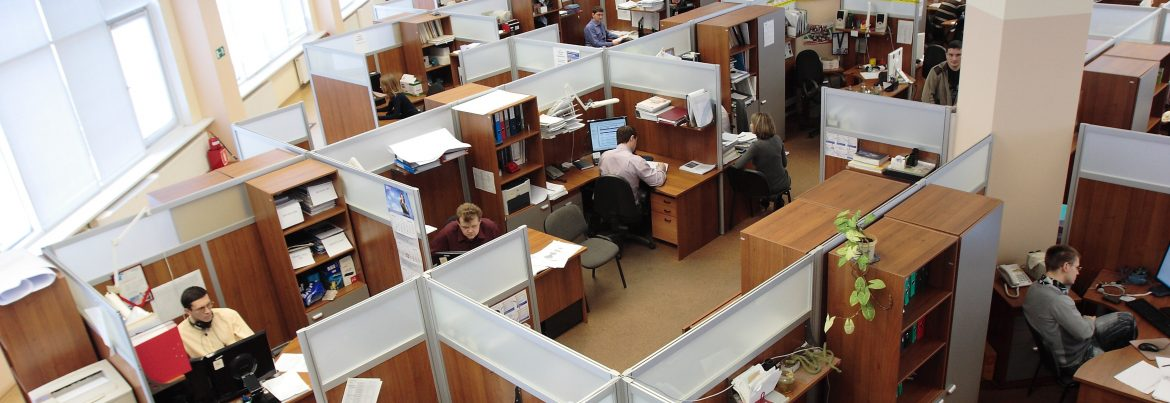 Ceiling view of an office full of cubicles and working employees at their desks.