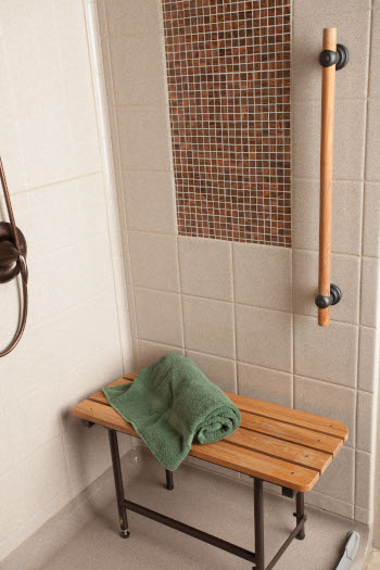 bestbath shower with recessesd tile and a teak bench.