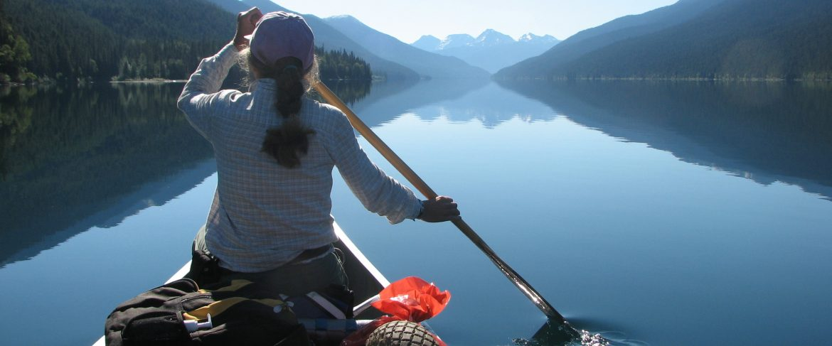 Cariboo Regional District. A woman rowing a canoe in a calm lake with mountains on either side and the background.