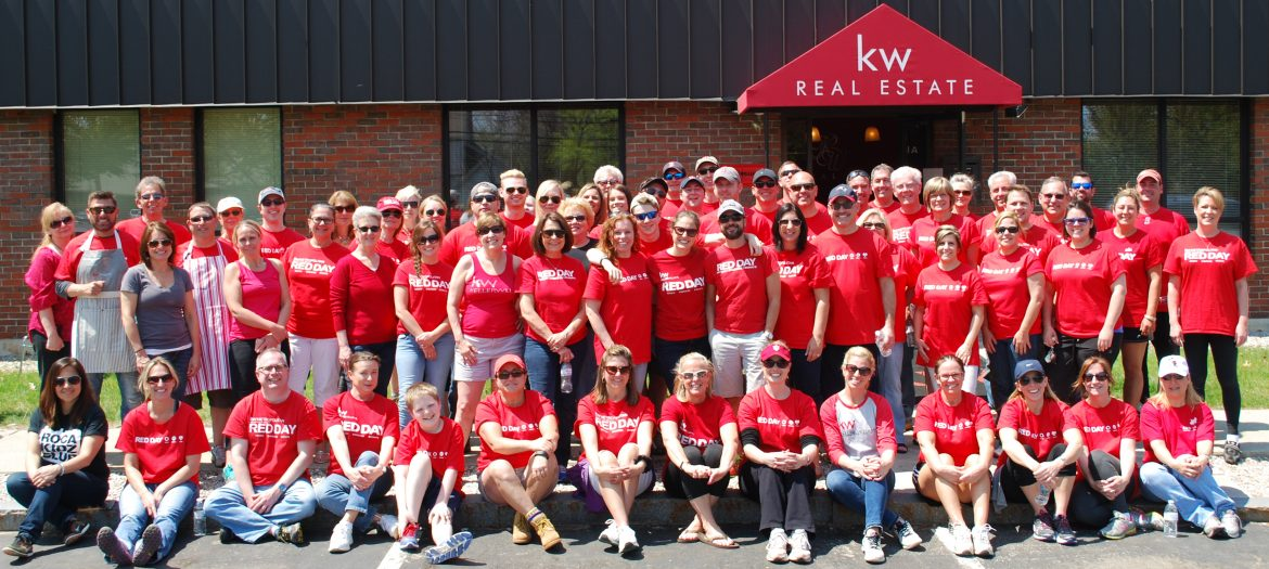 Keller Williams Realty Metropolitan. A group shot of employees out front of their office all in red Keller Williams Realty shirts.