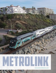 Metrolink brochure cover showing a train on tracks along a beach with multi story buildings behind on top of a hill.