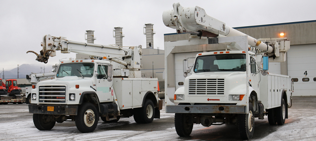 national electrical contractors association. Two electrical work trucks with booms parked in front of a building with garage doors.
