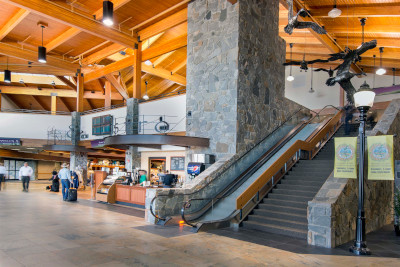 Bozeman Yellowstone International Airport inside showing shops, wood ceiling and an escalator and stairs.