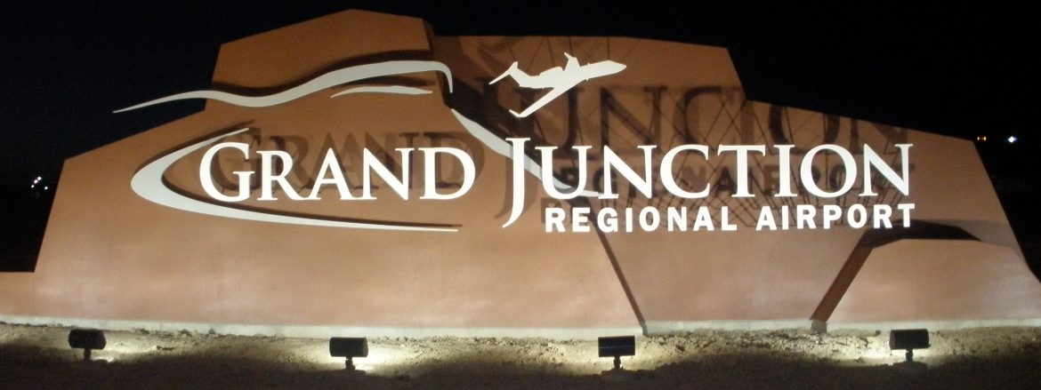 Grand Junction Regional Airport sign at night with lights shining on it.