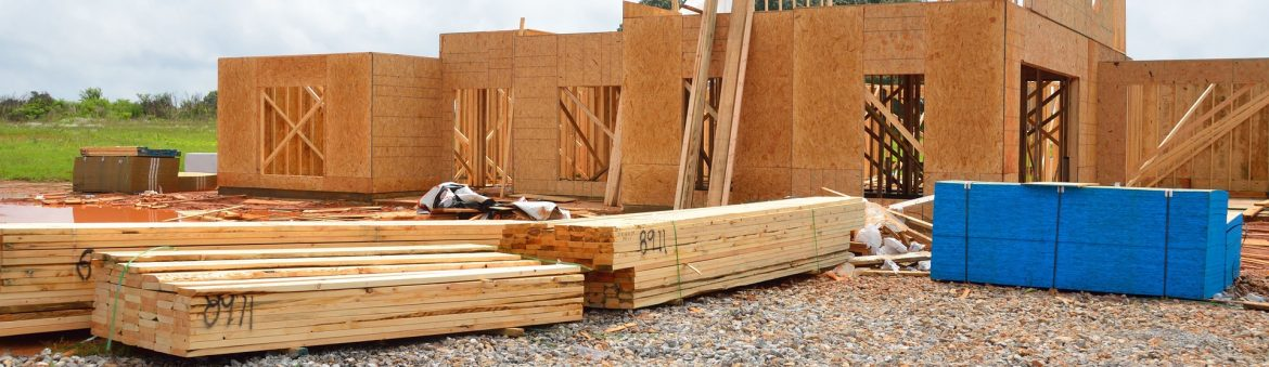 A new home construction site with wooden walls up and multiple stacks of lumber out front waiting to be used.