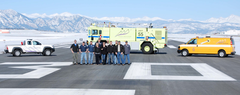 Rocky Mountain Metropolitan Airport operations staff in a group on the runway with vehicles position behind in the middle and on the left and right.