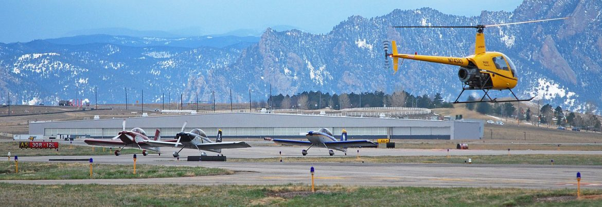 Rocky Mountain Metropolitan Airport a helicopter in flight with airplanes on the ground beyond, mountains in the background.