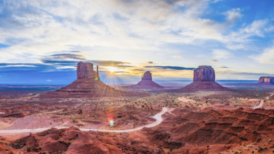 United States Environmental Protection Agency. Photo of mesas out west in the US with blue sky and scatted clouds, with the sun shining through.