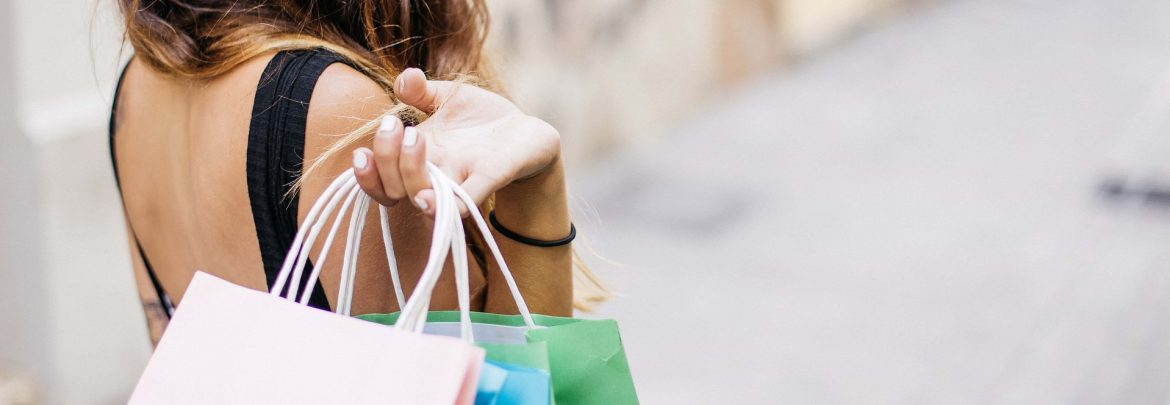 A woman with her hand holding shopping bags over her shoulder.