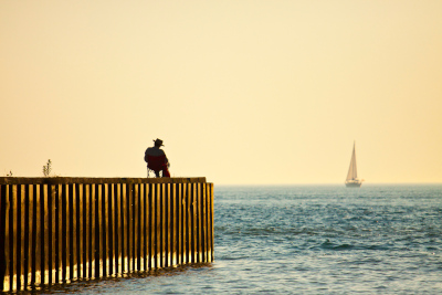 Goderich, Ontario; A min sitting on a pier with a sailboat in the distance on the water.