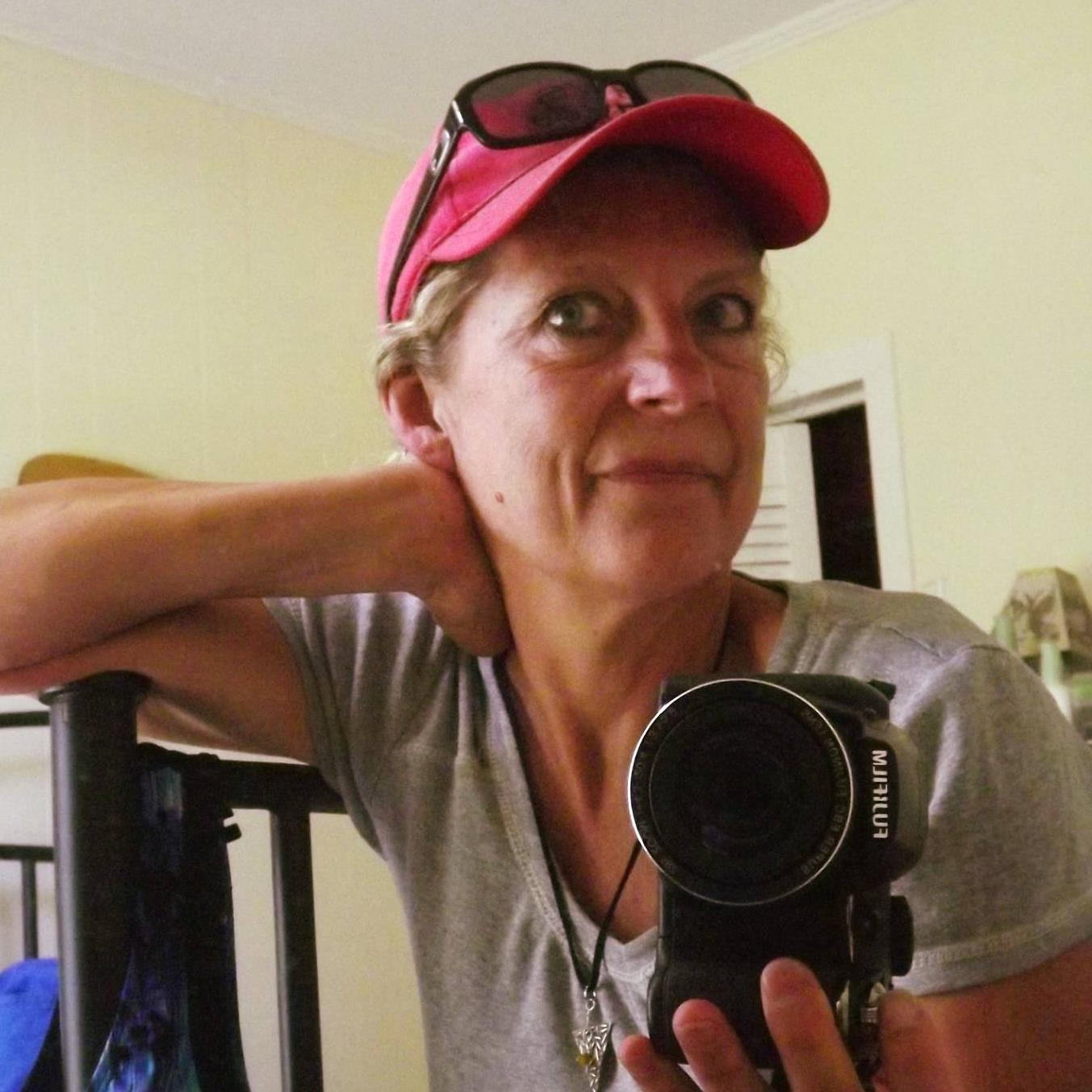Lorie Lee Steiner profile picture, with her wearing a hat with suglasses on top, and a camera in her hand.