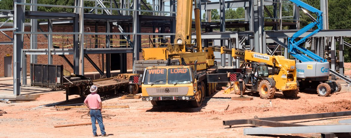 Mafic work site with multiple work vehicles including lifts and cranes.