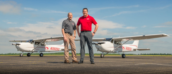 The Ohio State University Airport. Two men standing in front of two single engine airplanes.