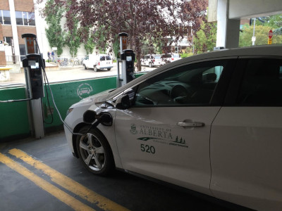 The University of Alberta. An Electric Vehicle (EV) parked and plugged into a charging station.