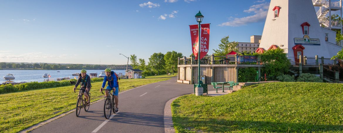 Fredericton, New Brunswick. Cyclers on a bike path along the water and a lighthouse on the right.